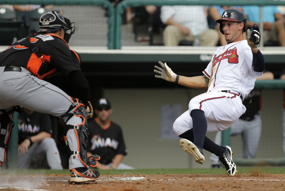 Photo - Atlanta Braves' Jordan Schafer, right, is tagged out by Miami Marlins catcher Kyle Skipworth, left, during the fifth inning of an exhibition spring training baseball game Monday, Feb. 25, 2013, in Kissimmee, Fla. (AP Photo/David J. Phillip)