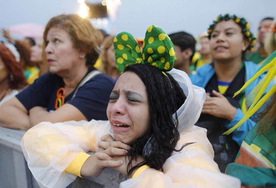 Photo - A Brazil soccer fan reacts in frustration as she watches her team play a World Cup semifinal match against Germany on a live telecast inside the FIFA Fan Fest area on Copacabana beach in Rio de Janeiro, Brazil, Tuesday, July 8, 2014. (AP Photo/Leo Correa)