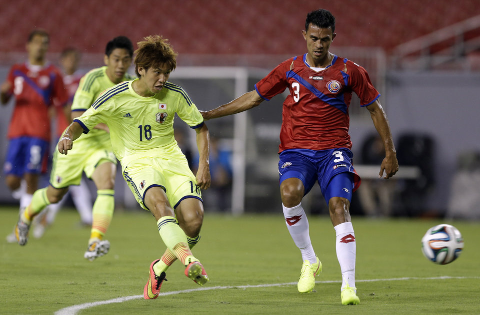Photo - Japan forward Yuya Osako (18) gets off a shot in front of Costa Rica defender Giancarlo Gonzalez (3) during the first half of a friendly soccer match Monday, June 2, 2014, in Tampa, Fla. (AP Photo/Chris O'Meara)