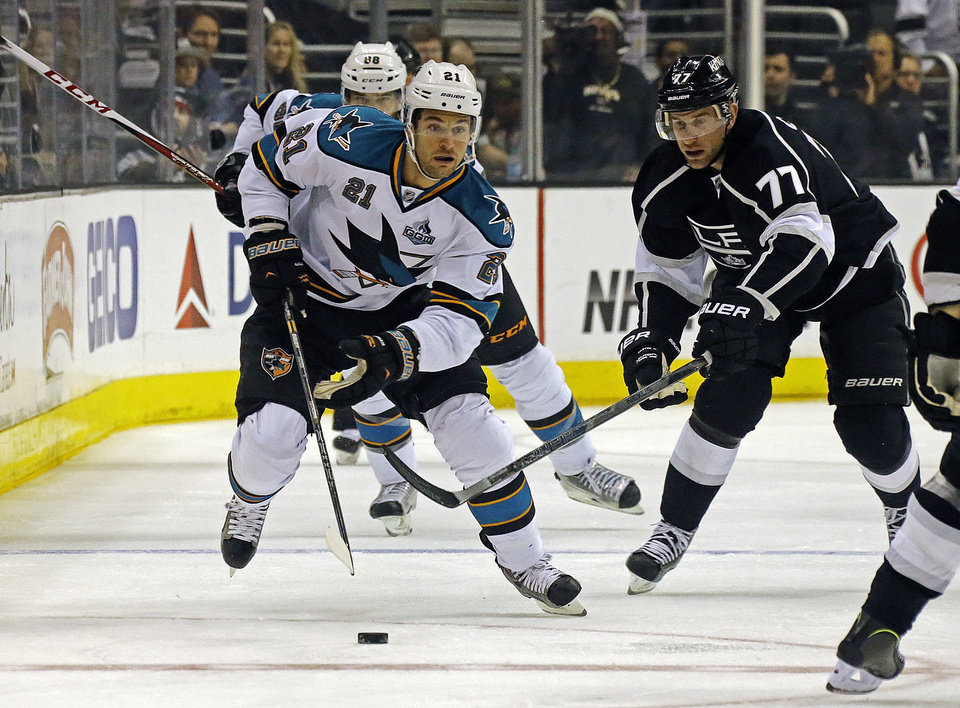 Photo - San Jose Sharks left wing T.J. Galiardi (21) and Los Angeles Kings center Jeff Carter (77) move the puck in the first period of an NHL hockey game in Los Angeles Saturday, April 27, 2013. AP Photo/Reed Saxon)