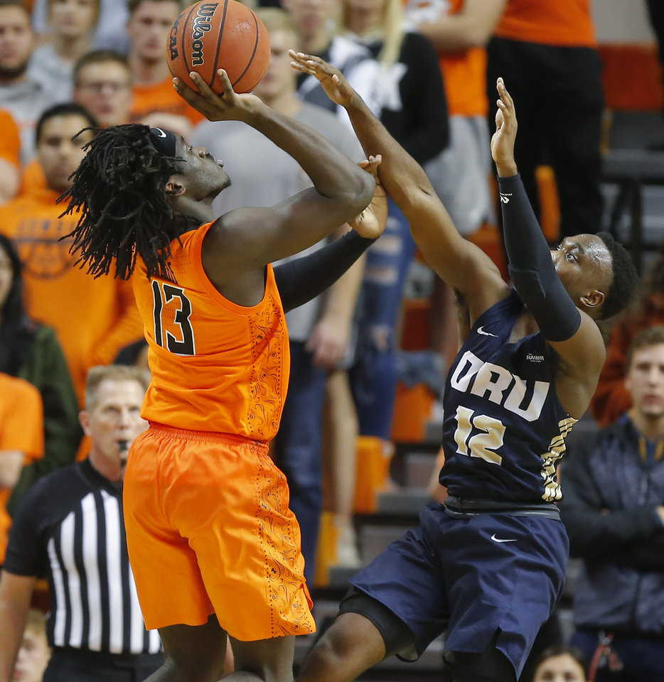 Photo - Oklahoma State's Isaac Likekele (13) shoots over R.J. Fuqua (12) of Oral Roberts during an NCAA basketball game between the Oklahoma State University Cowboys (OSU) and the Oral Roberts Golden Eagles (ORU) at Gallagher-Iba Arena in Stillwater, Okla., Wednesday, Nov. 6, 2019. Oklahoma State won 80-75. [Bryan Terry/The Oklahoman]