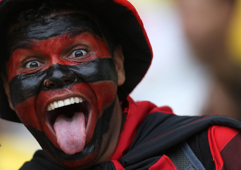 Photo - In this April 13, 2014 photo, a fan with his face painted in the colors of Flamengo's soccer team poses before a Rio de Janeiro state championship final soccer game with Vasco  at Maracana stadium in Rio de Janeiro, Brazil. Brazil expects a total of 3.7 million tourists during the World Cup, with 600,000 of those arriving from abroad. (AP Photo/Leo Correa)