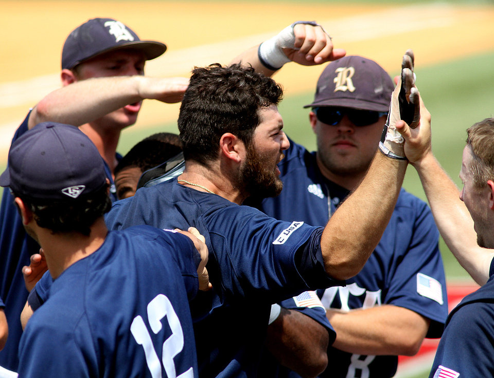 Photo - Rice's Michael Aquinois, center, is  congratulated as he crosses the plate after hitting a two-run homer against UTSA during an NCAA college baseball game in the Conference USA tournament championship game Sunday, May 25, 2014, in Hattiesburg, Miss.. Rice won the championship 11-5 and Aquino was also named as the tournament MVP. (AP Photo/George Clark)