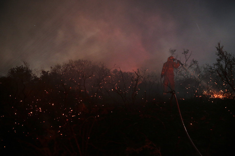 Photo - A firefighter puts out a spot fire while standing on a smoldering field on Wednesday, May 14, 2014, in San Marcos, Calif. Flames engulfed suburban homes and shot up along canyon ridges in one of the worst of several blazes that broke out Wednesday in Southern California during a second day of a sweltering heat wave, taxing fire crews who fear the scattered fires mark only the beginning of a long wildfire season. (AP Photo)