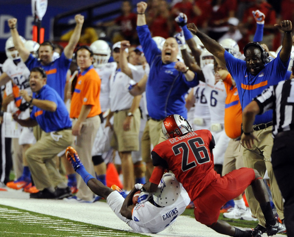 Boise State cornerback Jerrell Gavins (4) makes an interception in front of Georgia wide receiver Malcolm Mitchell (26) in the first half of an NCAA college football game on Saturday, Sept. 3, 2011 at the Georgia Dome in Atlanta. (AP Photo/David Tulis)