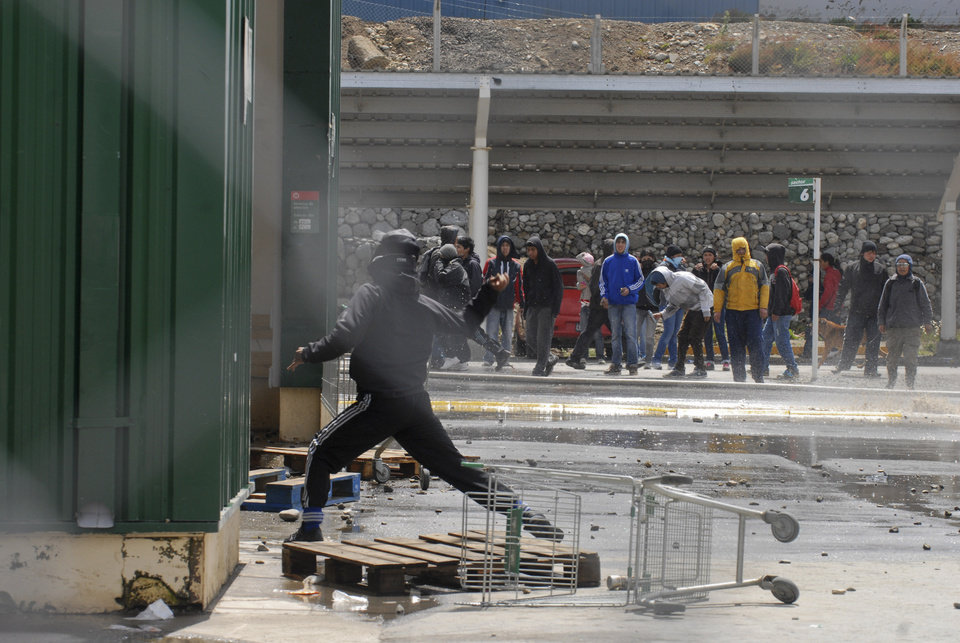 A looter throws stones against police officers during clashes at a supermarket in San Carlos de Bariloche, about 1.630 km southwest of Buenos Aires, Argentina, Thursday, Dec. 20, 2012. Hooded people looted at least three supermarkets and set a car on fire after claiming for food to celebrate Christmas in the city of Bariloche, part of Argentina's Patagonia region. (AP Photo/Diario Rio Negro)
