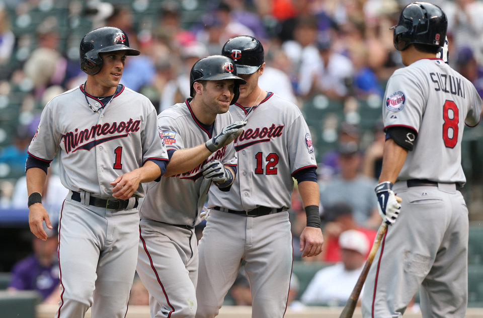 Photo - Minnesota Twins' Brian Dozier, second from left, is congratulated by teammates, from left, Sam Fuld, Chris Hermann and Kurt Suzuki after Dozier hit a three-run home run against the Colorado Rockies in the ninth inning of the Twins' 13-5 victory in an interleague baseball game in Denver on Sunday, July 13, 2014. (AP Photo/David Zalubowski)