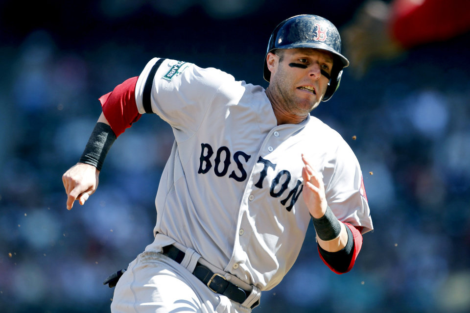 Photo -   Boston Red Sox's Dustin Pedroia comes around to score against the Seattle Mariners in the first inning of a baseball game, Monday, Sept. 3, 2012, in Seattle. (AP Photo/Elaine Thompson)