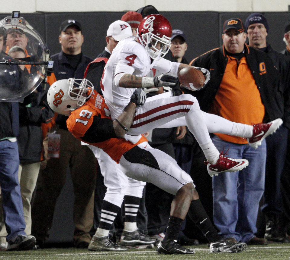 Photo - Oklahoma State's Brodrick Brown (19) brings down Oklahoma's Kenny Stills (4)during the Bedlam college football game between the University of Oklahoma Sooners (OU) and the Oklahoma State University Cowboys (OSU) at Boone Pickens Stadium in Stillwater, Okla., Saturday, Nov. 27, 2010. Photo by Bryan Terry, The Oklahoman