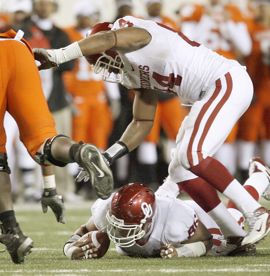 Photo - OU's Adrian Taylor recovers a fumble under Jeremy Beal in the fourth quarter of the college football game between the University of Oklahoma Sooners (OU) and Oklahoma State University Cowboys (OSU) at Boone Pickens Stadium on Saturday, Nov. 29, 2008, in Stillwater, Okla. STAFF PHOTO BY BRYAN TERRY