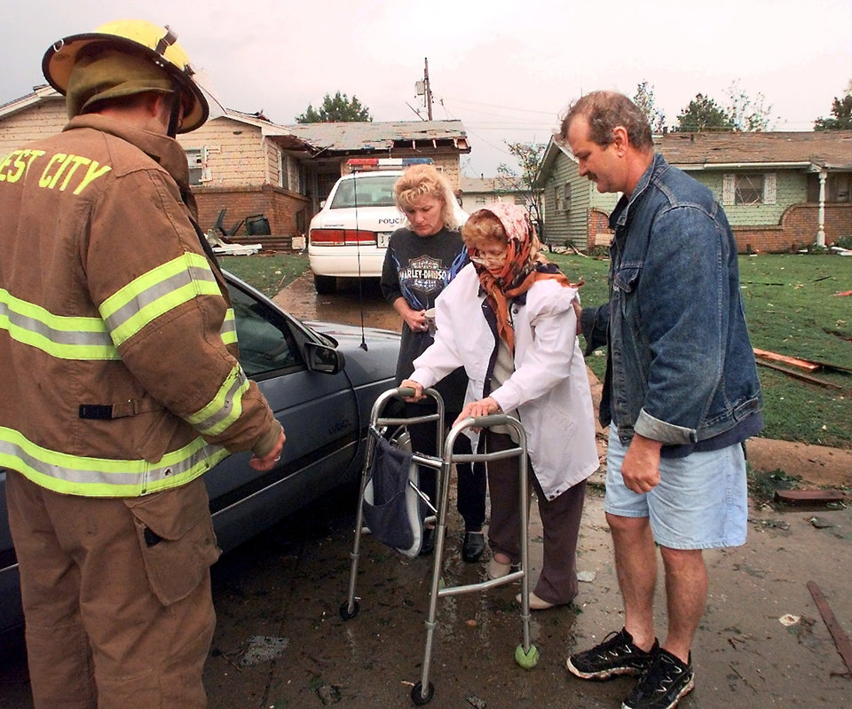 MAY 3, 1999 TORNADO: Tornado victims, damage: Coreen Schlanger is helped to a car by unidentified neighbors Tuesday morning.  A Midwest City Fire Department employee drove the woman to a shelter at the MWC Community Center.  Schlanger's home in the 6100 block of SE 3 was heavily damaged in Monday night's tornado.