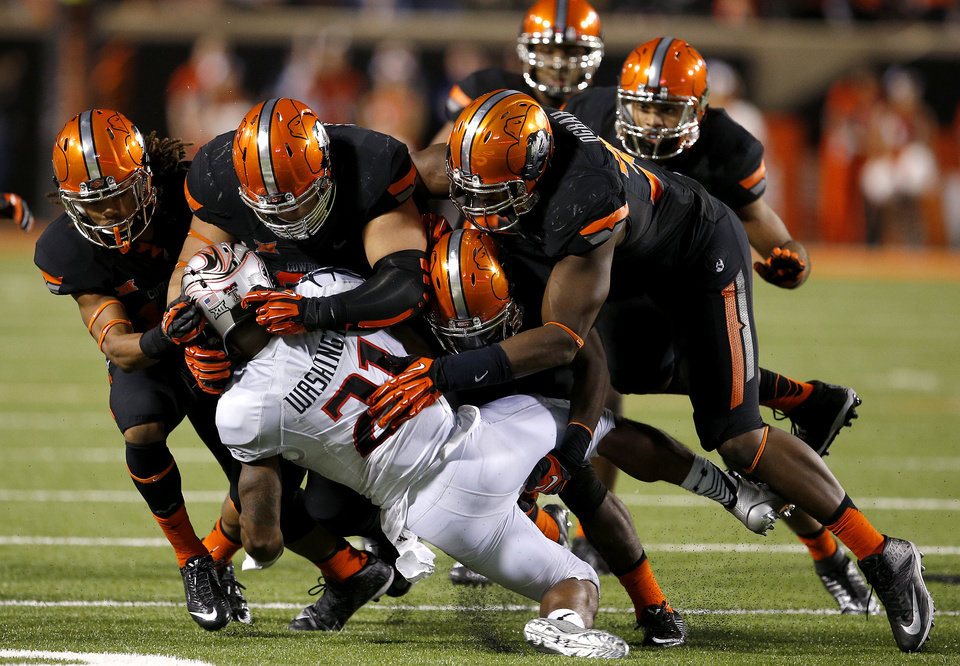 Photo - Oklahoma State's Ramon Richards (18), left, James Castleman (91), Larry Stephens (20), and Emmanuel Ogbah (38) bring down Texas Tech's DeAndre Washington (21) during a college football game between the Oklahoma State Cowboys (OSU) and the Texas Tech Red Raiders at Boone Pickens Stadium in Stillwater, Okla., Thursday, Sept. 25, 2014. Photo by Bryan Terry, The Oklahoman