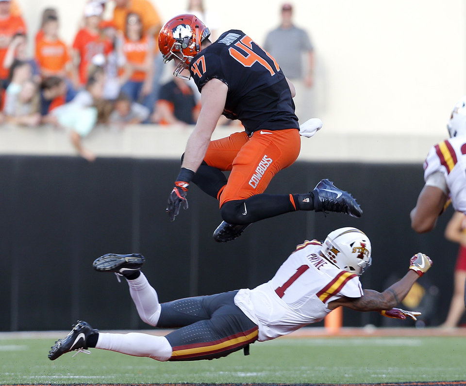 Photo - Oklahoma State's Blake Jarwin (47) leaps over Iowa State's D'Andre Payne (1) in the fourth quarter during a college football game between the Oklahoma State University Cowboys (OSU) and the Iowa State University at Boone Pickens Stadium in Stillwater, Okla., Saturday, Oct. 8, 2016. Photo by Sarah Phipps, The Oklahoman
