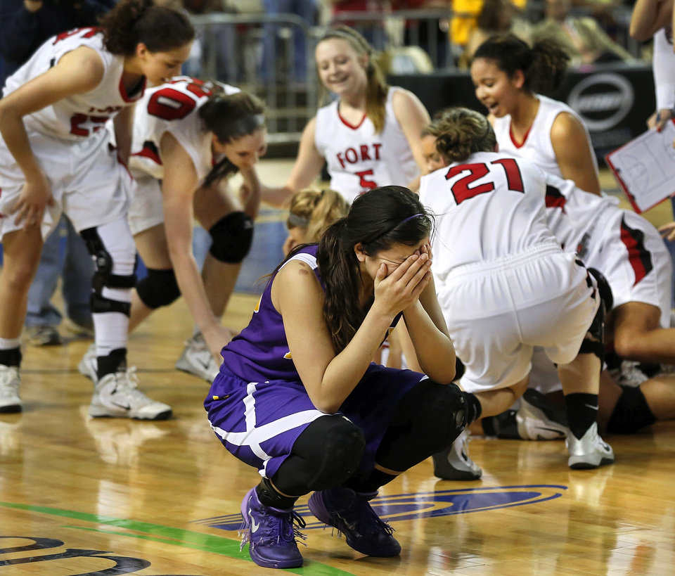 Photo - Anadarko junior Ashley Beatty covers her face and sobs while a victorious Ft. Gibson team celebrates behind her at the end of the Class 4A State championship game between Ft. Gibson and Anadarko at Jim Norick Arena at State Fair Park  on Saturday, Mar. 15, 2014. Ft. Gibson came from behind much of the second half to win 50-47.  Photo by Jim Beckel, The Oklahoman