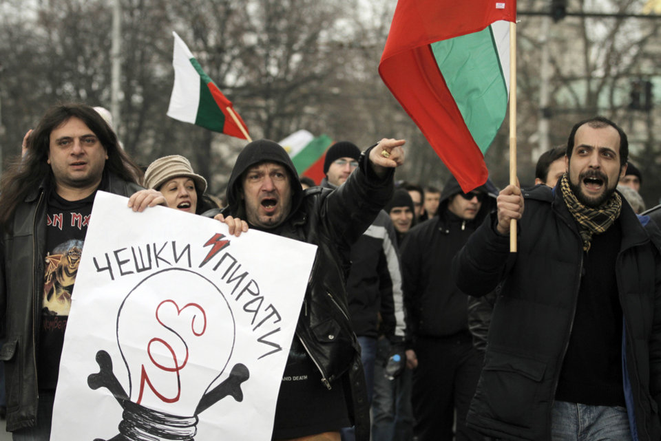 "Bulgarians shout slogans and carry poster reading ""CEZ - Czech pirates"" as they protest against higher electricity and heating bills, in Sofia,  Sunday, Feb. 17, 2013. Thousands of angry Bulgarians chanted ""mafia"" and ""resignation""  demanded the expulsion of the three foreign-controlled power distributors that control the local market: Czech Republic's CEZ and Energo-Pro, and Austria's EVN   (AP Photo/Valentina Petrova)"
