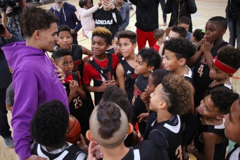 Photo -  Atlanta Hawks guard Trae Young speaks with kids after announcing a partnership Feb. 18, 2019, with Santa Fe Family Life Center, which will serve as the official home of the Trae Young Elite Basketball Program. [Doug Hoke/The Oklahoman]