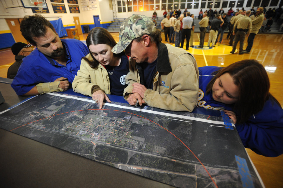 Imn a photo made Nov. 29, 2012,from left  Brandon Barton, Heather Bailey, Chris Clegg and Gabby Clegg  look over a map showing the area of concern for citizens after inproperly stored explosives wer discovered  on nearby Camp Minden, La.     Discovery of the improperly stored material led to evacuation of the nearby town of Doyline  and prompted a criminal investigation of Explo Systems Inc.  (AP Photo/The Shreveport Times,Douglas Collier) MAGS OUT; MANDATORY CREDIT SHREVEPORTTIMES.COM;  NO SALES   MBO