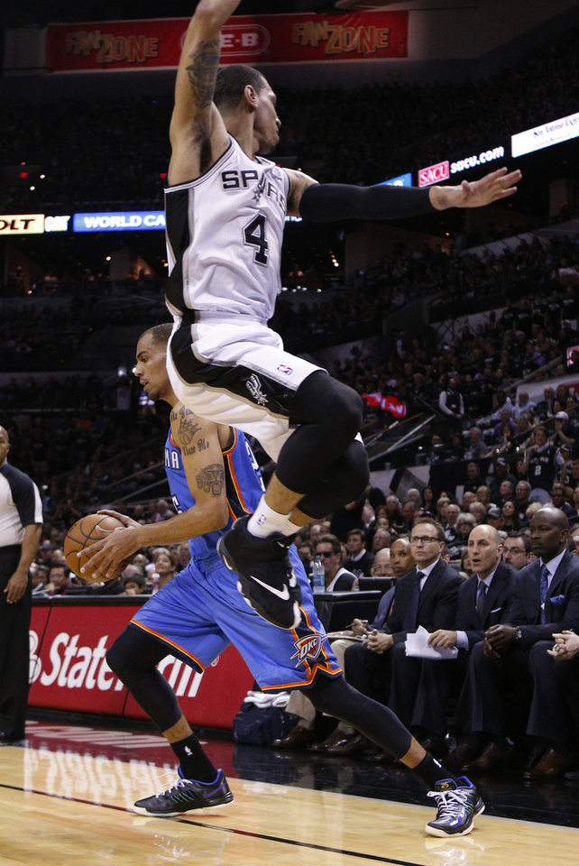 Photo - San Antonio's Danny Green (4) leaps past Oklahoma City's Thabo Sefolosha (25) during Game 1 of the Western Conference Finals in the NBA playoffs between the Oklahoma City Thunder and the San Antonio Spurs at the AT&T Center in San Antonio, Monday, May 19, 2014. Photo by Sarah Phipps, The Oklahoman