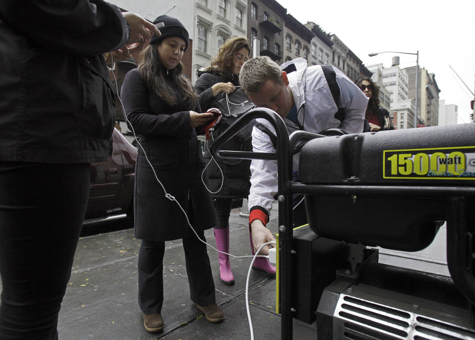 People in New York\'s Tribeca neighborhood, without power because of superstorm Sandy, wait for a chance to charge their mobile phones on an available generator setup on a sidewalk, Tuesday, Oct. 30, 2012. Sandy, the storm that made landfall Monday, caused multiple fatalities, halted mass transit and cut power to more than 6 million homes and businesses. (AP Photo/Richard Drew) ORG XMIT: NYRD118