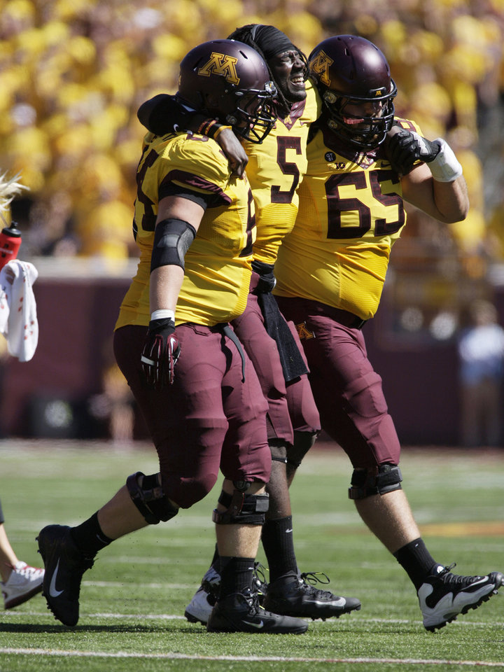 Photo -   Minnesota quarterback MarQueis Gray (5) is helped off the field by teammates Josh Campion (65) and Caleb Bak (64) after being injured during the first half of an NCAA football game against Western Michigan, Saturday, Sept. 15, 2012, in Minneapolis. (AP Photo/Paul Battaglia)