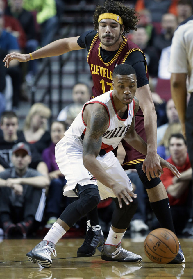Photo - Portland Trails Blazers guard Damian Lillard, front, looks for room to maneuver as Cleveland Cavaliers center Anderson Varejao, from Brazil, defends during the first half of an NBA basketball game in Portland, Ore., Wednesday, Jan. 15, 2014. (AP Photo/Don Ryan)