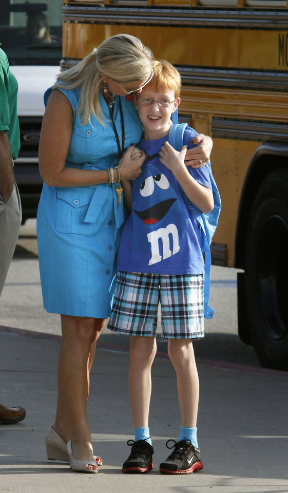 Photo - Principal Amy Simpson hugs a student as Plaza Towers Elementary School students begin their first day of classes Friday in their temporary location at Central Junior High in Moore.  Photo by Paul Hellstern, The Oklahoman  PAUL HELLSTERN - Oklahoman