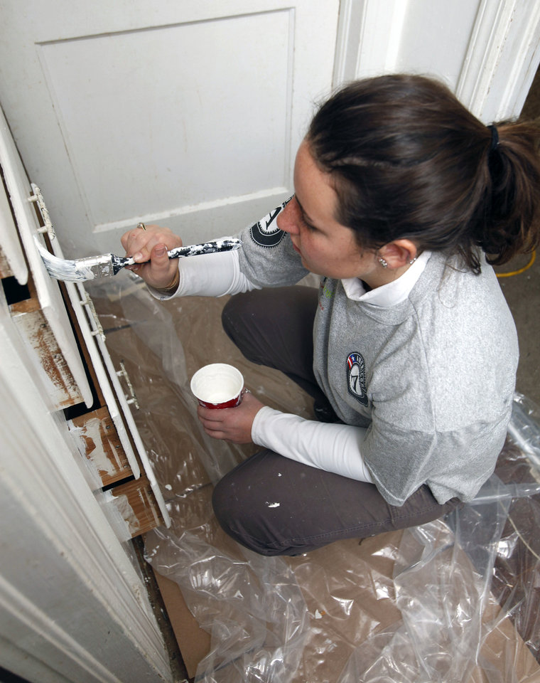 Photo - Katie Savarese repaints drawer fronts as part of a weeklong renovation project in northeast Oklahoma City.  By Paul Hellstern, The Oklahoman  PAUL HELLSTERN - Oklahoman