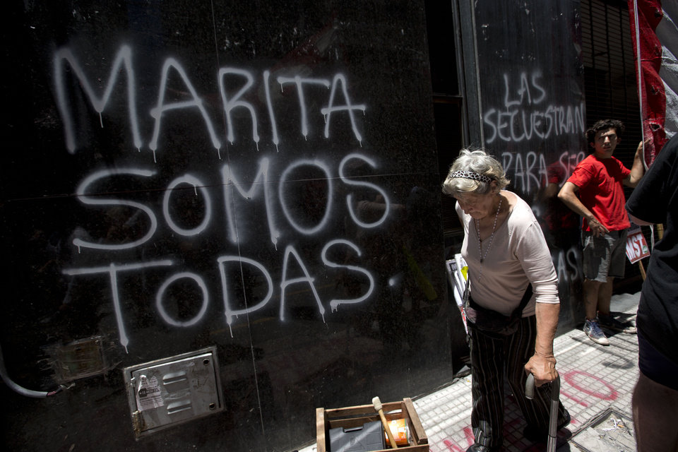 "A woman walks by graffiti that reads in Spanish ""We're all Marita"" written by protesters outside the building used by government representatives of Argentina's Tucuman province during a demonstration in Buenos Aires, Argentina, Wednesday, Dec. 12, 2012. Activists are protesting the Tuesday decision by judges that found all defendants innocent in a high-profile case of an Argentine woman, Maria de los Angeles ""Marita"" Veron, who was allegedly kidnapped and forced into prostitution a decade ago in Tucuman. (AP Photo/Victor R. Caivano)"