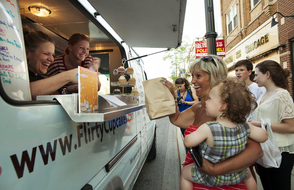 In this July 12, 2012 photo, Tiffany Kurtz, left, owner of the Flirty Cupcakes food truck, sells to customers in Chicago. An ordinance proposed by Chicago Mayor Rahm Emanuel would finally allow trucks to cook and prepare food on board. While the trucks are already allowed on Chicago�s streets, current rules prohibit operators from so much as putting hot sauce on a taco for a customer. The full City Council could vote on the proposal as soon as next week. (AP Photo/Sitthixay Ditthavong)