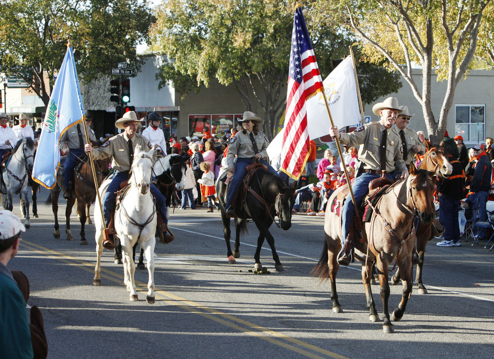Photo - Members of the Payne County Sheriff's Dept. ride in the Oklahoma State Cowboy's homecoming parade in downtown Stillwater, OK, Saturday, Oct. 29, 2011. By Paul Hellstern, The Oklahoman