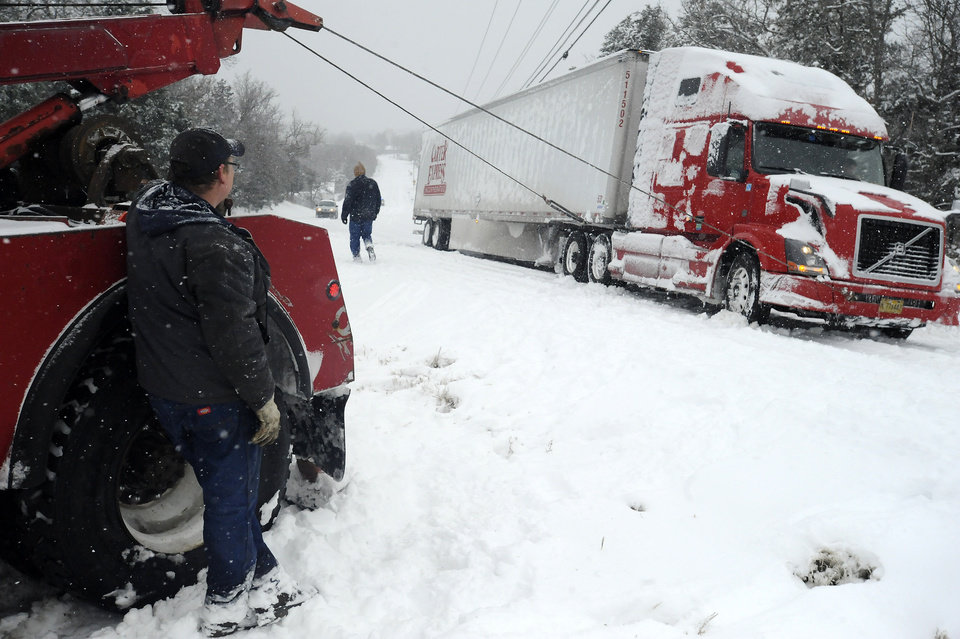 Photo - Jim Dobbs, left, helps pull a tractor trailer rig out of a ditch Friday, Dec. 6, 2013, in Henderson, Ark. The icy storm plowing across the country is delaying shipments of everything from Christmas presents to cooking grease. (AP Photo/The Baxter Bulletin, Kevin Pieper)   NO SALES