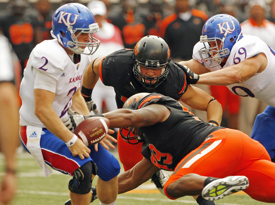 Photo - Oklahoma State's Richetti Jones (99) causes a fumble by Kansas' Jordan Webb (2) during a college football game between the Oklahoma State University Cowboys (OSU) and the University of Kansas Jayhawks (KU) at Boone Pickens Stadium in Stillwater, Okla., Saturday, Oct. 8, 2011.  The Cowboys recovered. Photo by Steve Sisney, The Oklahoman