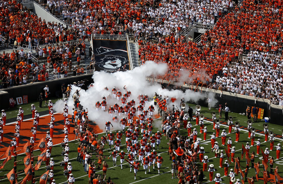 Photo - Oklahoma State runs onto the field before  a college football game between the Oklahoma State Cowboys (OSU) and the Pitt Panthers at Boone Pickens Stadium in Stillwater, Okla., Saturday, Sept. 17, 2016. Photo by Sarah Phipps, The Oklahoman