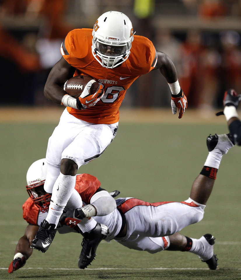 Photo - Oklahoma State's Desmond Roland (26) gets by Lamar's Tyrus McGlothen (4) during a college football game between the Oklahoma State University Cowboys (OSU) and the Lamar University Cardinals at Boone Pickens Stadium in Stillwater, Okla., Saturday, Sept. 14, 2013. Photo by Sarah Phipps, The Oklahoman