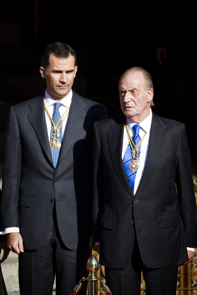 Photo - FILE - In this Tuesday, Dec. 27, 2011, file photo, Spain's King Juan Carlos, right, and Crown Prince Felipe, left, wait for their cars after the official opening of Parliament, in Madrid. Spain's King Juan Carlos plans to abdicate and pave the way for his son, Crown Prince Felipe, to take over, Spanish Prime Minister Mariano Rajoy told the country Monday in an announcement broadcast nationwide. The 76-year-old Juan Carlos oversaw his country's transition from dictatorship to democracy but has had repeated health problems in recent years. (AP Photo/Daniel Ochoa de Olza, File)