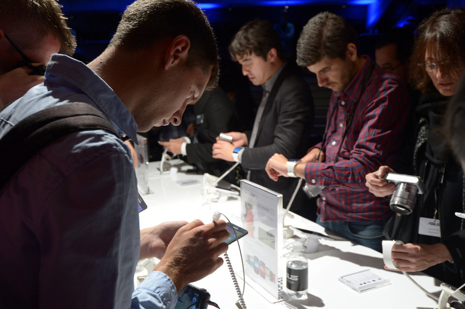 Photo - People test  new Samsung products   at the IFA, one of the world's largest trade fairs for consumer electronics and electrical home appliances in Berlin, Germany, Wednesday, Sept. 3, 2014. The IFA takes place in Berlin from Sept. 5 until Sept. 10, 2014.   (AP Photo/dpa, Rainer Jensen)