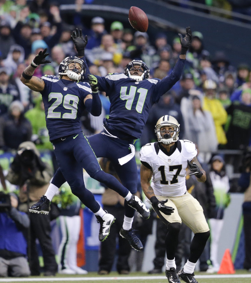 Photo - Seattle Seahawks free safety Earl Thomas (29) and cornerback Byron Maxwell (41) jump for a pass that was caught by New Orleans Saints wide receiver Robert Meachem (17) during the fourth quarter of an NFC divisional playoff NFL football game in Seattle, Saturday, Jan. 11, 2014. The Seahawks won 23-15. (AP Photo/John Froschauer)