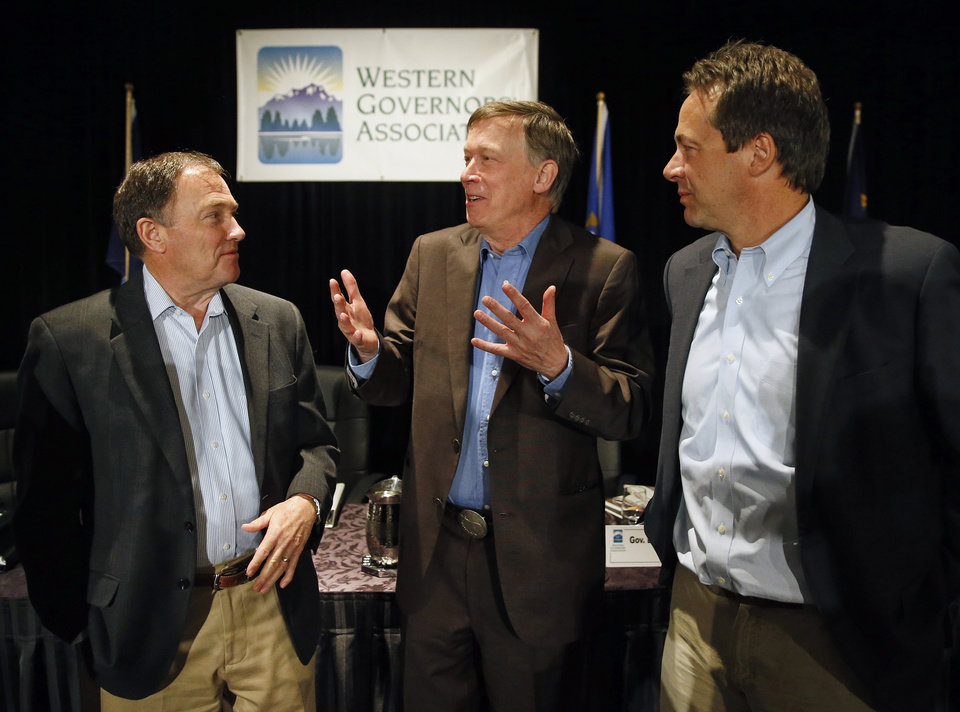 Photo - Colo. Gov. John Hickenlooper, center, talks with fellow Governors Gary Herbert of Utah, left, and Montana's Steve Bullock, during the annual Western Governors' Association Meeting, at the Broadmoor Hotel in Colorado Springs, Tuesday, June 10, 2014. Ten governors from western states attended the second day of the conference Tuesday, discussing common regional issues. (AP Photo/Brennan Linsley)