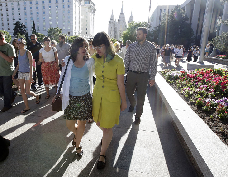 Photo - Kate Kelly, right, walks with a supporter after addressing her supporters at the Church Office Building of the Church of Jesus Christ of Latter-day Saints during a vigil Sunday, June 22, 2014, in Salt Lake City. Kelly was shocked to find out earlier this month from her bishop that she is facing excommunication from The Church of Jesus Christ of Latter-day Saints, of which she is a lifelong member. (AP Photo/Rick Bowmer)