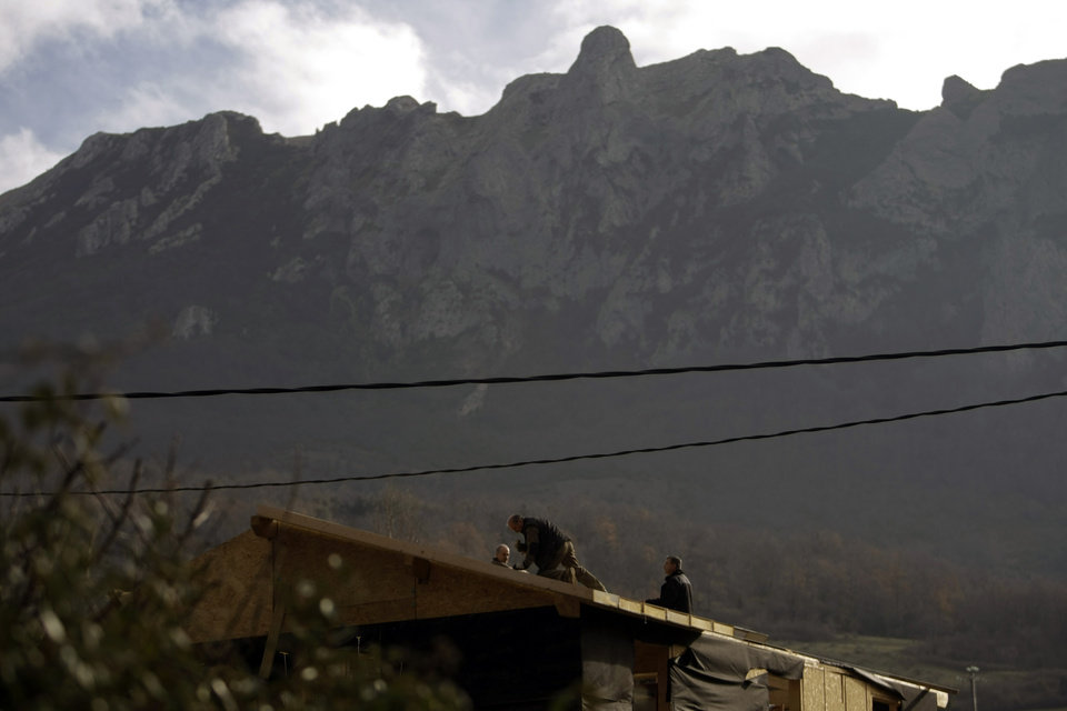 Photo - People work on a roof backdropped by the Pic de Bugarach mountain in the town of Bugarach, France, Thursday, Dec. 20, 2012. The clock is ticking down to Dec. 21, the supposed end of the Mayan calendar, and from China to California to Mexico, thousands are getting ready for what they think is going to be a fateful day. The sleepy town of Bugarach, nestled in the French Pyrenees mountains, is bracing for the arrival of hundreds of New Age enthusiasts and UFO believers that want to witness the end of the Mayan Long Count calendar. (AP Photo/Marko Drobnjakovic)