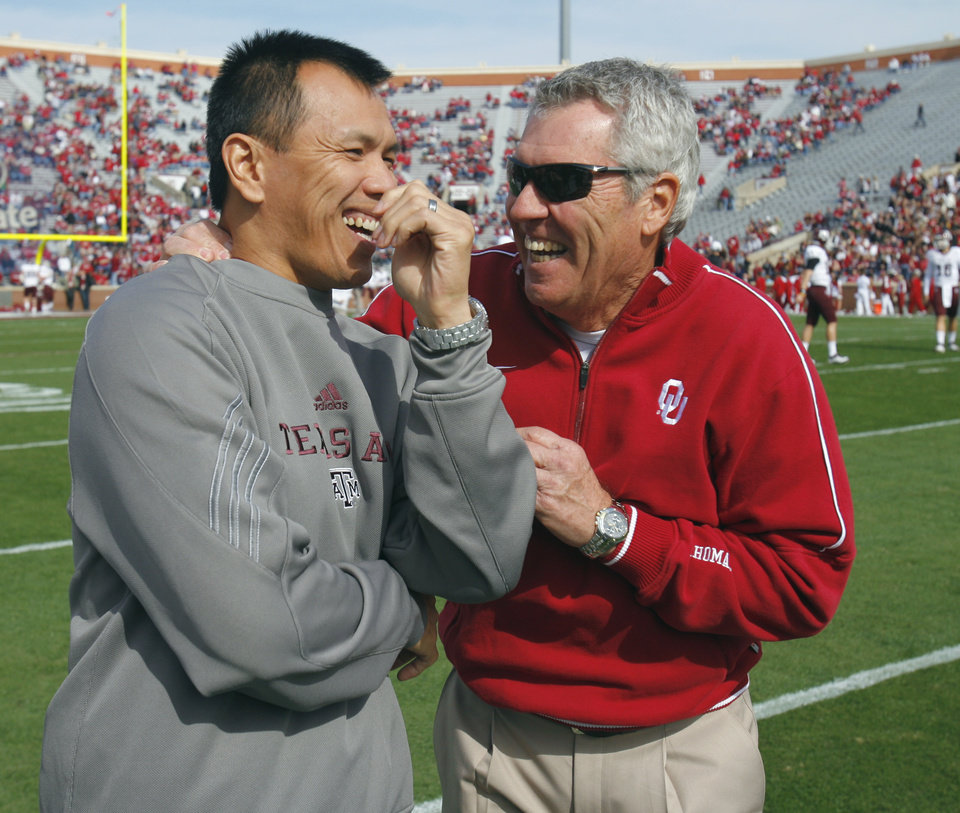 Photo - Sooner assistant head coach Bobby Jack Wright talks with former Dallas Cowboy and Texas A&M player Dat Nguyen before the college football game between the Texas A&M Aggies and the University of Oklahoma Sooners (OU) at Gaylord Family-Oklahoma Memorial Stadium on Saturday, Nov. 5, 2011, in Norman, Okla. Photo by Steve Sisney, The Oklahoman