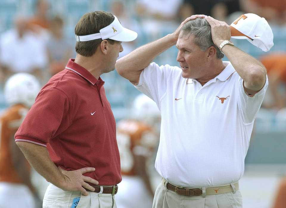 Photo - DALLAS, Saturday,10/11/2003: University of Oklahoma vs. University  of Texas college football at Cotton Bowl.   UT coach Mack Brown, right, and OU head coach Bob Stoops talk before the game at midfield.  Staff photo by Jim Beckel.
