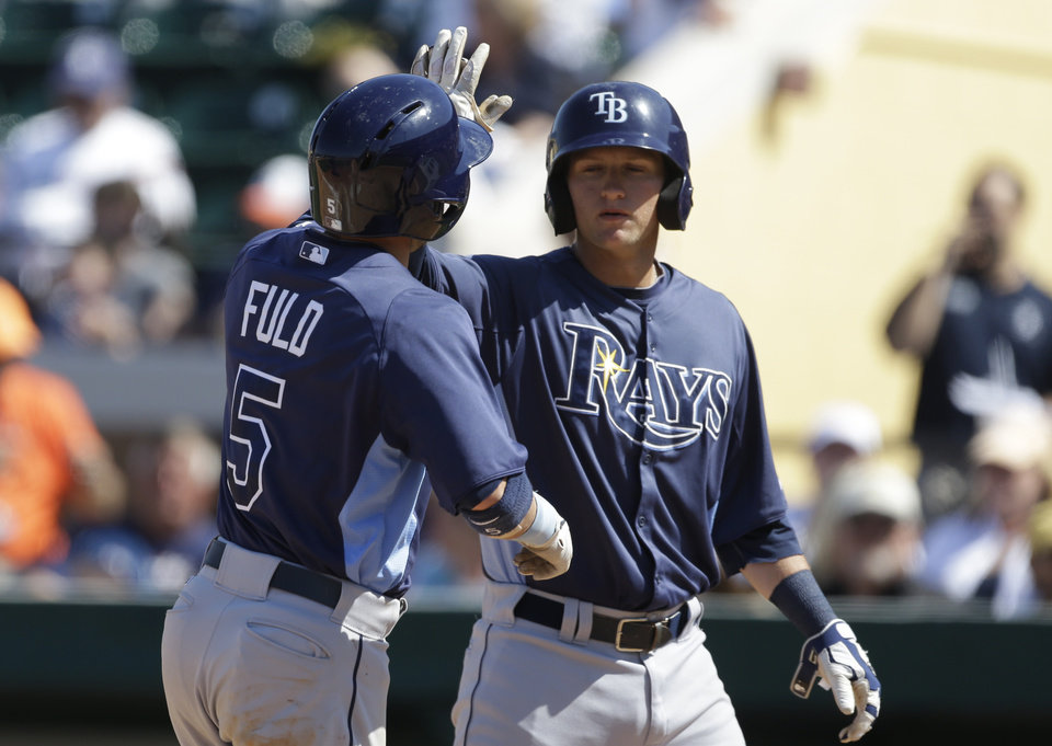 Photo - Tampa Bay Rays' Sam Fuld (5) is congratulated by teammate Jake Hager after hitting a two-run home run during the eighth inning of an exhibition spring training baseball game against the Detroit Tigers, Friday, March 29, 2013, in Lakeland, Fla. (AP Photo/Carlos Osorio)