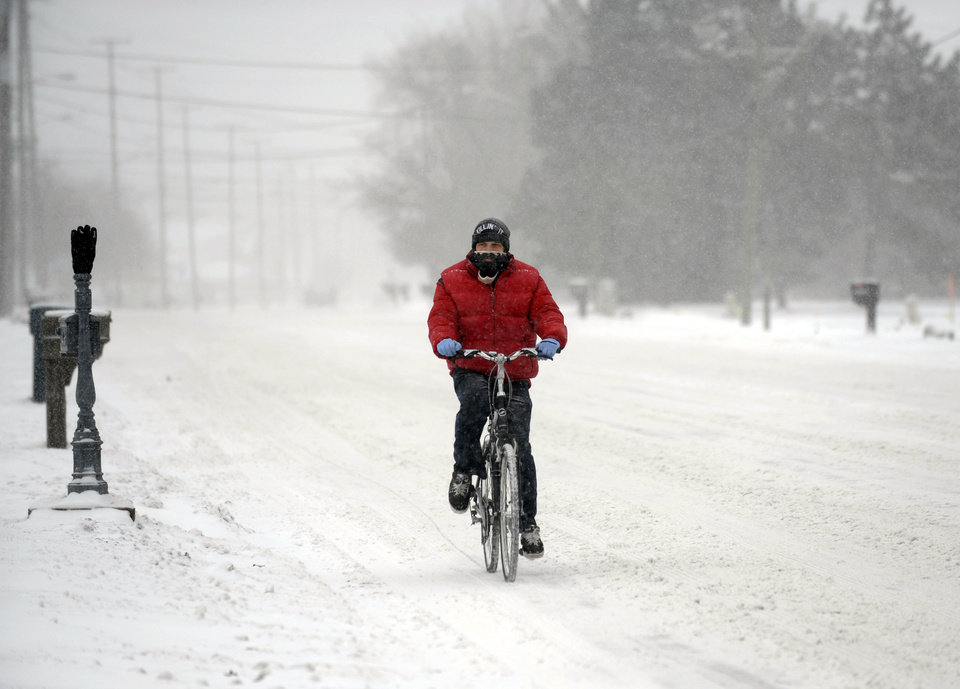 Photo - Jordan Beaudrie rides his bike in the snow in St. Clair Shores, Mich., Thursday, Jan. 2, 2014.   A multi-day storm dropped up to a foot of snow on parts of Michigan, causing crashes and spinouts on roadways. Snowfall began Tuesday and continued Thursday morning. (AP Photo/Detroit News,  David Coates) DETROIT FREE PRESS OUT; HUFFINGTON POST OUT, MADATORY CREDIT