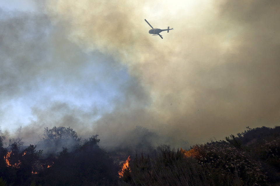 Photo - A helicopter flies over burning vegetation as it nears homes Wednesday, May 14, 2014, in Carlsbad, Calif. More wildfires broke out Wednesday in San Diego County — threatening homes in Carlsbad and forcing the evacuations of military housing and an elementary school at Camp Pendleton — as Southern California is in the grip of a heat wave. (AP Photo)