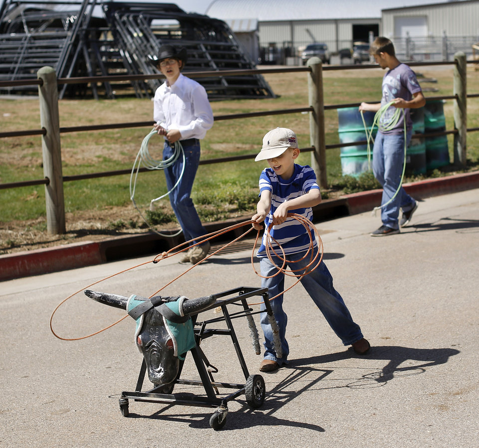 Photo - Gavin Straka, 8, of El Reno puts his rope just where he wants it while practicing roping techniques on a roping dummy with team ropers Cole Campbell of Pauls Valley, left, and Curt Richardson of Elmore City. The older boys were taking advantage of some free time before they had to show their animals at the Oklahoma Youth Expo at State Fair Park on Tuesday,   March 18, 2014. Straka is too young to compete in the expo. Photo by Jim Beckel, The Oklahoman