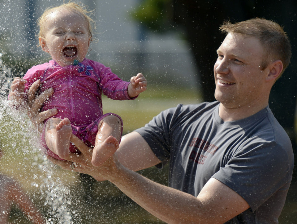 Photo -   Ryan Reddy of Ballston Spa, N.Y., holds his 1-year-old daughter Elliette Reddy over a spray of water while cooling off from the heat at the Geyser Park Fountain in Saratoga Springs, N.Y. Friday, July 6, 2012. The National Weather Service reported late Thursday that the record-breaking heat that has baked the nation's midsection for several days was slowly moving into the mid-Atlantic states and Northeast. (AP Photo/The Daily Gazette, Peter R. Barber) TROY, SCHENECTADY; SARATOGA SPRINGS; ALBANY AND AMSTERDAM OUT