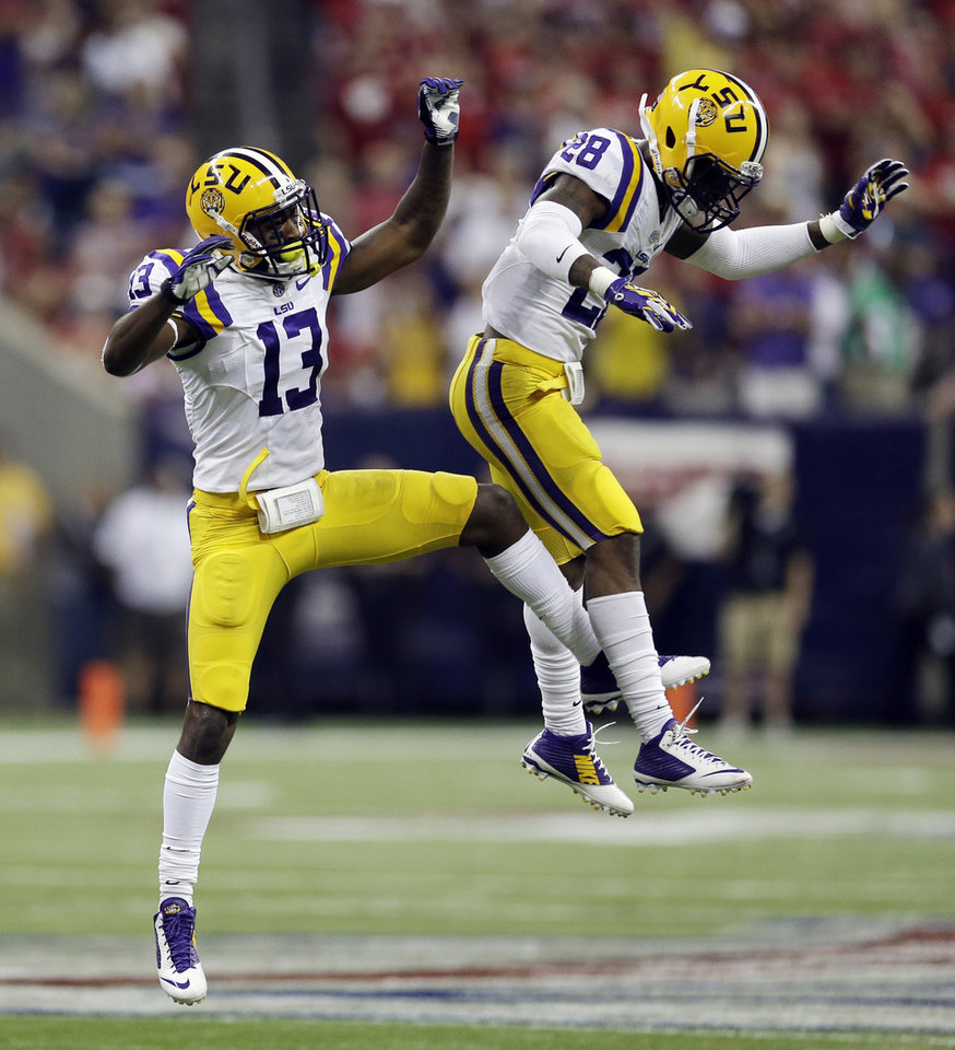 Photo - LSU's Dwayne Thomas (13) and Jalen Mills (28) celebrate a defensive stop during the second half of an NCAA college football game Saturday, Aug. 30, 2014, in Houston. (AP Photo/David J. Phillip)