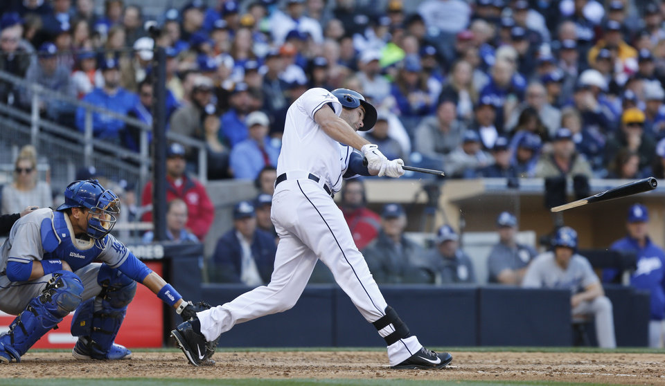 Photo - San Diego Padres' Seth Smith has his bat snapped but manages to drive the ball into center field for a base hit in the sixth inning of baseball game against the Los Angeles Dodgers Tuesday, April 1, 2014, in San Diego.  (AP Photo/Lenny Ignelzi)