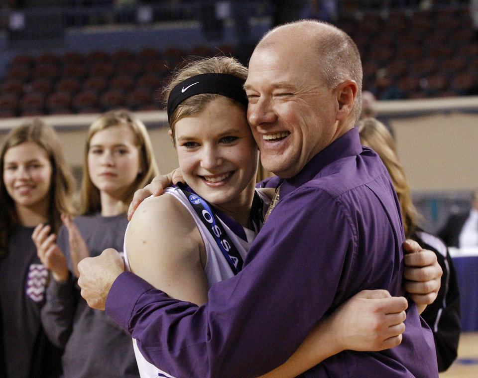 Photo - Okarche junior Kenadey Grellner smiles as she is hugged by Okarche Schools Superintendent Rob Friesen after  presenting her a championship medal at the end of  the  Class B girls high school basketball championship game in the Jim Norick Arena at State Fair Park on  Saturday, March 8, 2014.   Okarche defeated Red Oak, 66-41. Photo by Jim Beckel, The Oklahoman